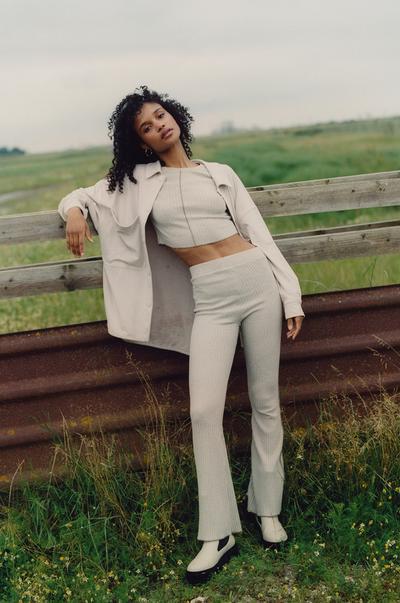 Model met een beige overhemd, top en broek