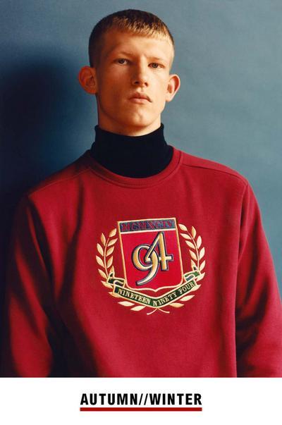 Model im roten Pullover mit Markenwappen von Primark