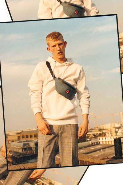 Model wearing a cream jumper, check trousers and bum bag