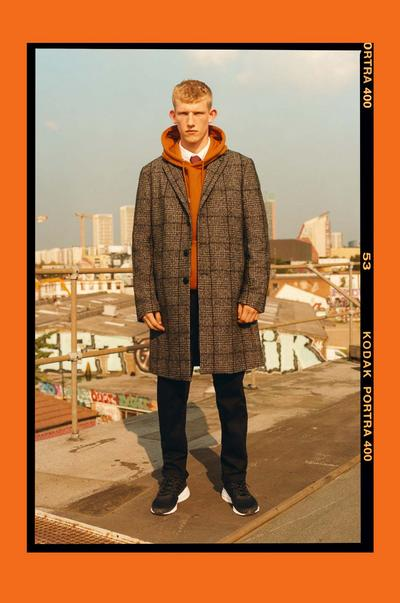 Model wearing an oversized check coat and orange hoodie