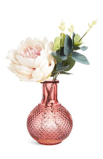 Mittelgroße Kunstblumen und dekoratives Grün in einer rosafarbenen Vase