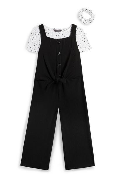 Črne hlače z naramnicami, pikčasta bela srajca in elastika za lase za deklice