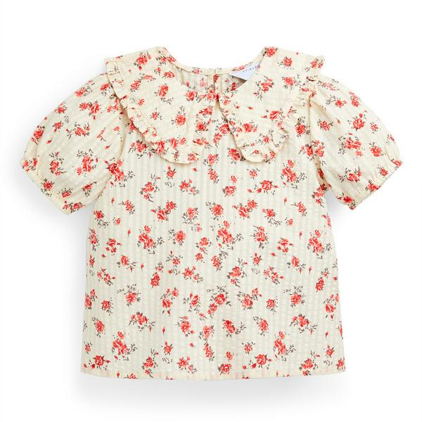Blusa de color marfil con flores para niña pequeña